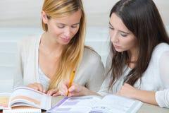 Dos adolescencias con los cuadernos que se preparan para la escuela en casa Imagenes de archivo
