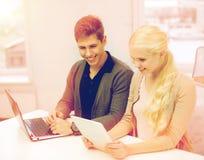Dos adolescencias con PC del ordenador portátil y de la tableta en la escuela Imagen de archivo libre de regalías