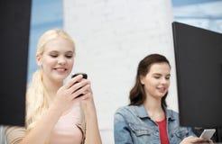 Dos adolescencias con smartphones en clase del ordenador Imágenes de archivo libres de regalías