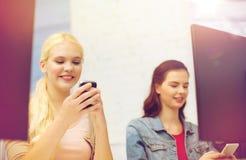 Dos adolescencias con smartphones en clase del ordenador Imagen de archivo