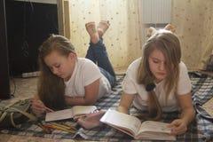 Dos adolescencias de la muchacha que leen un libro y que dibujan mientras que miente en el piso en casa Imágenes de archivo libres de regalías