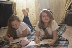 Dos adolescencias de la muchacha que pasan el tiempo en casa que lee un libro y que dibuja mientras que mienten en el piso Foto de archivo libre de regalías