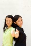 Dos adolescencias femeninas que dan los pulgares para arriba Foto de archivo libre de regalías