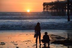 Dos adolescencias miran la puesta del sol por el embarcadero foto de archivo libre de regalías