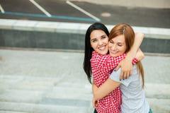 Dos adolescencias que abrazan en la calle Imagen de archivo libre de regalías