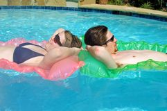 Dos adolescencias que flotan de nuevo a la parte posterior en una piscina suburbana Imagen de archivo