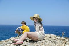 Dos adolescencias que se sientan en el top de una montaña con el océano azul en vagos Imagen de archivo