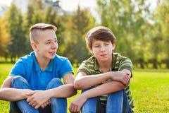 Dos adolescencias que se sientan junto en prado verde Imagenes de archivo