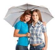 Dos adolescente-muchachas con el paraguas Fotos de archivo libres de regalías