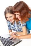 Dos adolescente-muchachas con la computadora portátil Imagen de archivo libre de regalías