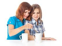 Dos adolescente-muchachas están bebiendo té Imagen de archivo