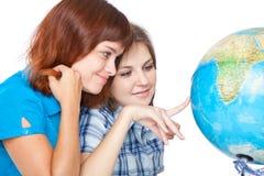 Dos adolescente-muchachas están mirando el globo Imágenes de archivo libres de regalías