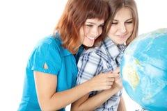 Dos adolescente-muchachas están mirando el globo Imagenes de archivo