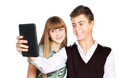 Dos adolescentes alegres que miran fijamente en la tablilla Imágenes de archivo libres de regalías