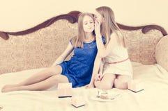 Dos adolescentes bonitos con el pelo largo wispering Imagenes de archivo