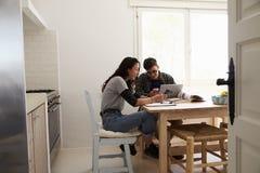 Dos adolescentes con el ordenador portátil usando smartphones en la tabla de cocina Fotos de archivo libres de regalías