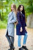 Dos adolescentes con el pelo largo en otoño cubren al aire libre Foto de archivo