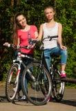 Dos adolescentes con la bicicleta en un parque Fotografía de archivo