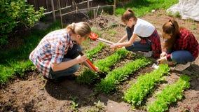 Dos adolescentes con la madre que trabaja en jardín Imágenes de archivo libres de regalías