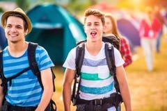 Dos adolescentes con las mochilas que llegan el festival de música Foto de archivo libre de regalías