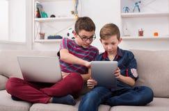 Dos adolescentes con los artilugios en el sofá en casa Foto de archivo