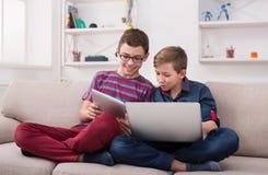 Dos adolescentes con los artilugios en el sofá en casa Fotografía de archivo