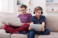 Dos adolescentes con los artilugios y los auriculares en el sofá en casa Imágenes de archivo libres de regalías