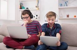Dos adolescentes con los artilugios y los auriculares en el sofá en casa Imagenes de archivo