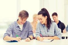 Dos adolescentes con los cuadernos en la escuela Fotos de archivo