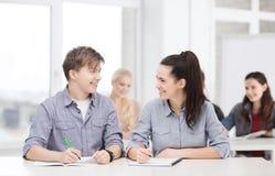 Dos adolescentes con los cuadernos en la escuela Foto de archivo