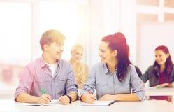 Dos adolescentes con los cuadernos en la escuela Imagen de archivo