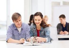 Dos adolescentes con los cuadernos y el libro en la escuela Fotos de archivo libres de regalías