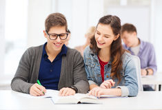 Dos adolescentes con los cuadernos y el libro en la escuela Foto de archivo