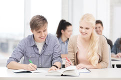 Dos adolescentes con los cuadernos y el libro en la escuela Imagenes de archivo
