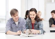 Dos adolescentes con los cuadernos y el libro en la escuela Foto de archivo libre de regalías