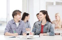 Dos adolescentes con los cuadernos y el libro en la escuela Imagen de archivo libre de regalías