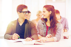 Dos adolescentes con los cuadernos y el libro en la escuela Imagen de archivo