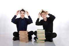 Dos adolescentes con los libros en su cabeza Foto de archivo libre de regalías