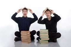 Dos adolescentes con los libros en su cabeza Fotos de archivo