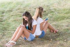Dos adolescentes con los teléfonos celulares se están sentando en hierba Fotografía de archivo