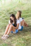 Dos adolescentes con los teléfonos celulares se están sentando en hierba Fotografía de archivo libre de regalías