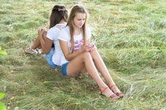 Dos adolescentes con los teléfonos celulares se están sentando en hierba Imagen de archivo libre de regalías