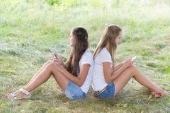 Dos adolescentes con los teléfonos celulares se están sentando en hierba Foto de archivo libre de regalías