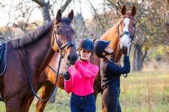 Dos adolescentes con su caballo en parque Imagen de archivo libre de regalías