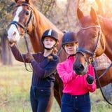 Dos adolescentes con su caballo en parque Imagen de archivo