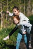 Dos adolescentes de los amigos de muchachas de las hermanas que se divierten en el parque Imagen de archivo