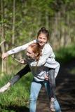 Dos adolescentes de los amigos de muchachas que se montan que se divierte en el parque en el verano Imágenes de archivo libres de regalías