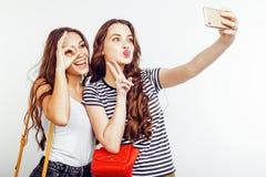Dos adolescentes de los mejores amigos junto que se divierten, presentación emocional en el fondo blanco, sonrisa feliz de los be Imagenes de archivo