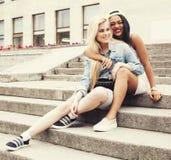 Dos adolescentes delante del edificio de la universidad que sonríen, teniendo Fotografía de archivo libre de regalías