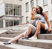 Dos adolescentes delante del edificio de la universidad que sonríen, teniendo Fotografía de archivo